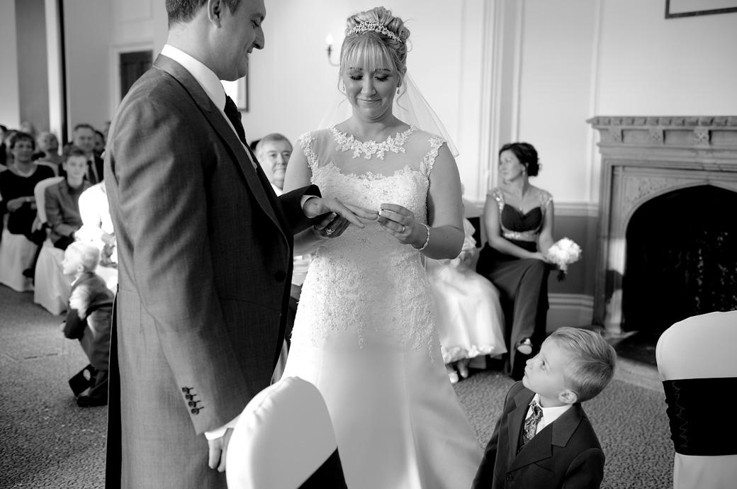 A smiling Horsley Towers Bride puts the ring on the Groom as their little son watches from below in this fun wedding picture captured by Surrey Lane wedding photographers