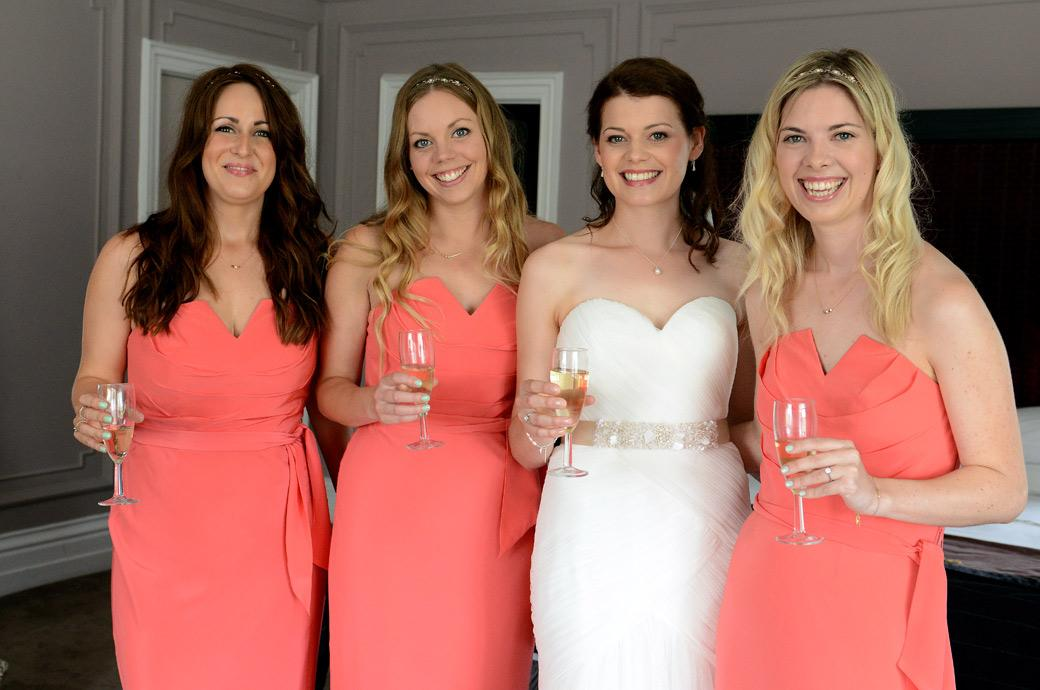 All smiles from the beautiful Bride and her pretty in pink Bridesmaids in this sweet celebratory wedding photograph taken at Surrey wedding venue Horsley Towers