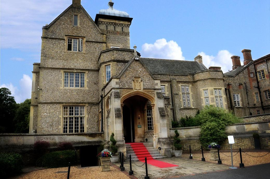 The red carpet welcoming the Bride and Groom and guests in this wedding photograph taken on the morning of the Big Day at the fascinating Surrey wedding venue Horsley Towers