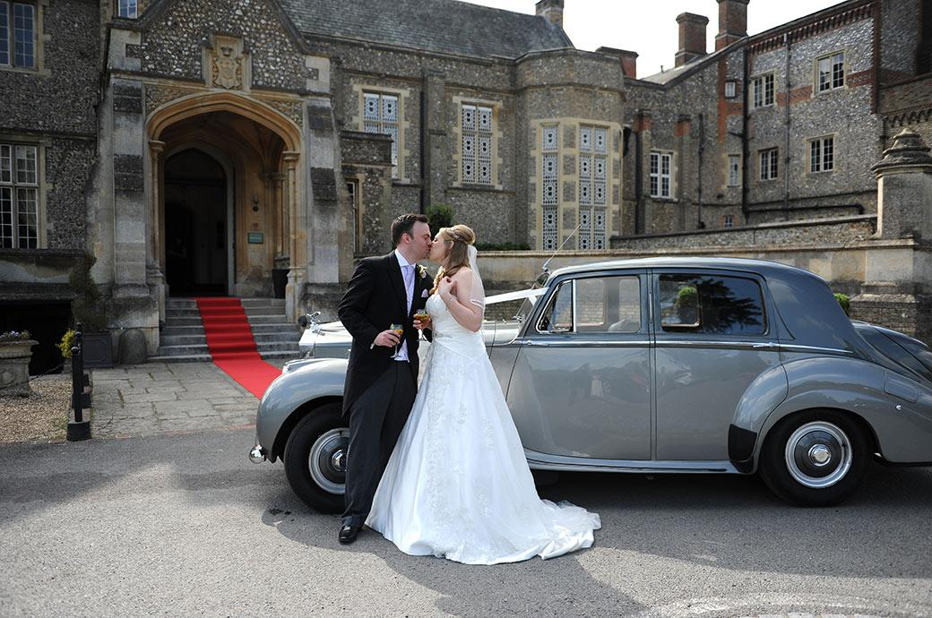 Newlyweds kiss in front of their grey Rolls Royce with the red carpet leading to the front door of Surrey wedding venue Horsley Towers in the background