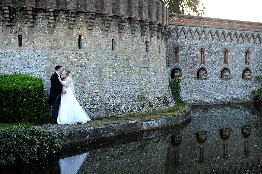 Romantic moment captured at the fantastical Horsley Towers in Surrey as the young lovers kiss in front of the majestic flint stone walls by the lake