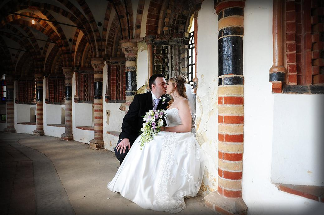 A romantic moment to share as the bride and groom sit on one of the seats in the multi brick coloured cloisters and kiss at the Horsley Towers Surrey wedding venue