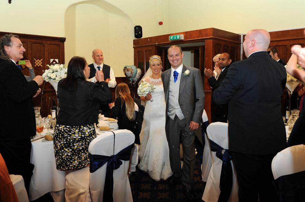 Smiles, cheering and applause captured in Horsley Towers in this Surrey wedding picture taken as the happy couple walk in for the wedding breakfast in the Great Hall