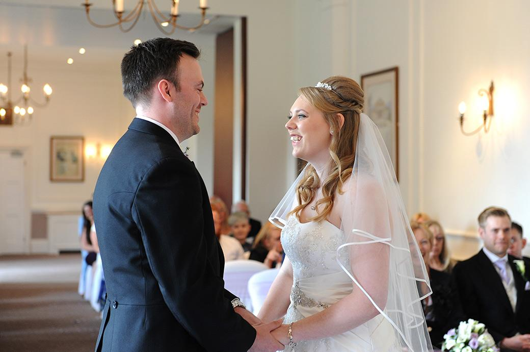 Overjoyed Bride and Groom holding hands in the Sopwith Room at Horsley Towers Surrey with big smiles on their faces as they are announced husband and wife