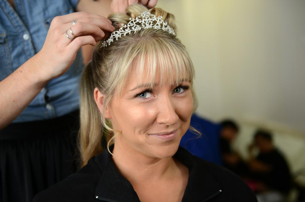 Happy smiling Bride captured in this wedding photo as she has the final adjustments to her hair taken by Surrey Lane wedding photographers at the delightful Horsley Towers