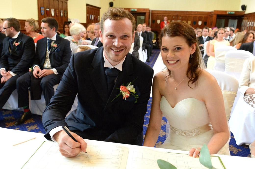 Relaxed smiles for the happy couple as they sign the marriage register captured in this wedding photograph in the Great Hall at the wonderful  Surrey wedding venue Horsley Towers