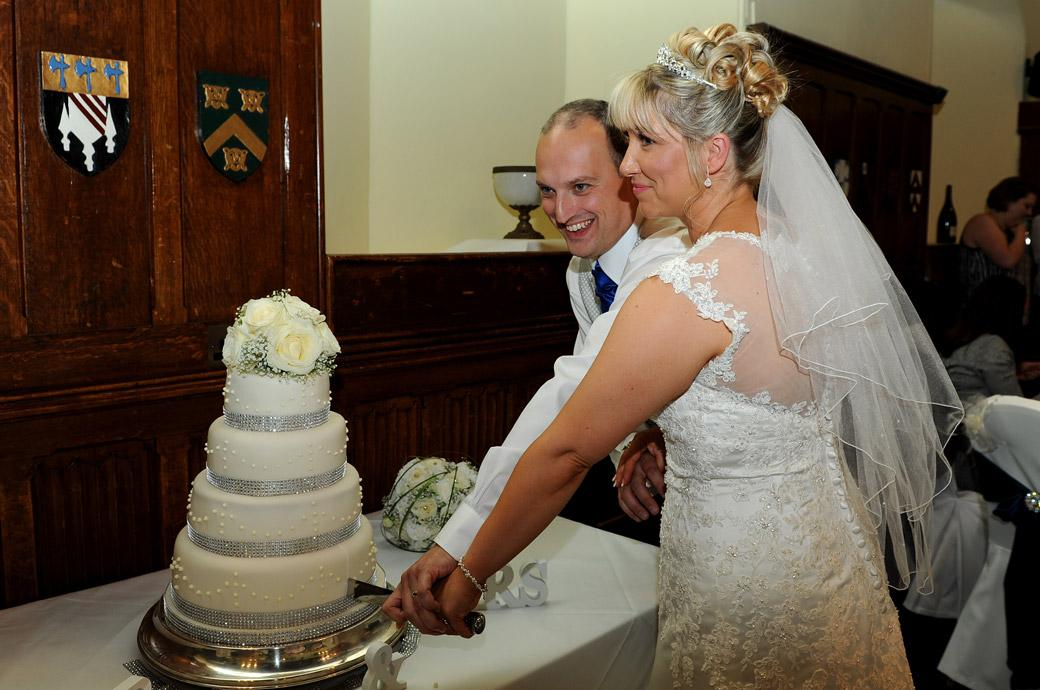 A smiling Bride and Groom finish cutting the cake in this wedding picture taken in the Great Hall at Horsley Towers by a Surrey Lane wedding photographer