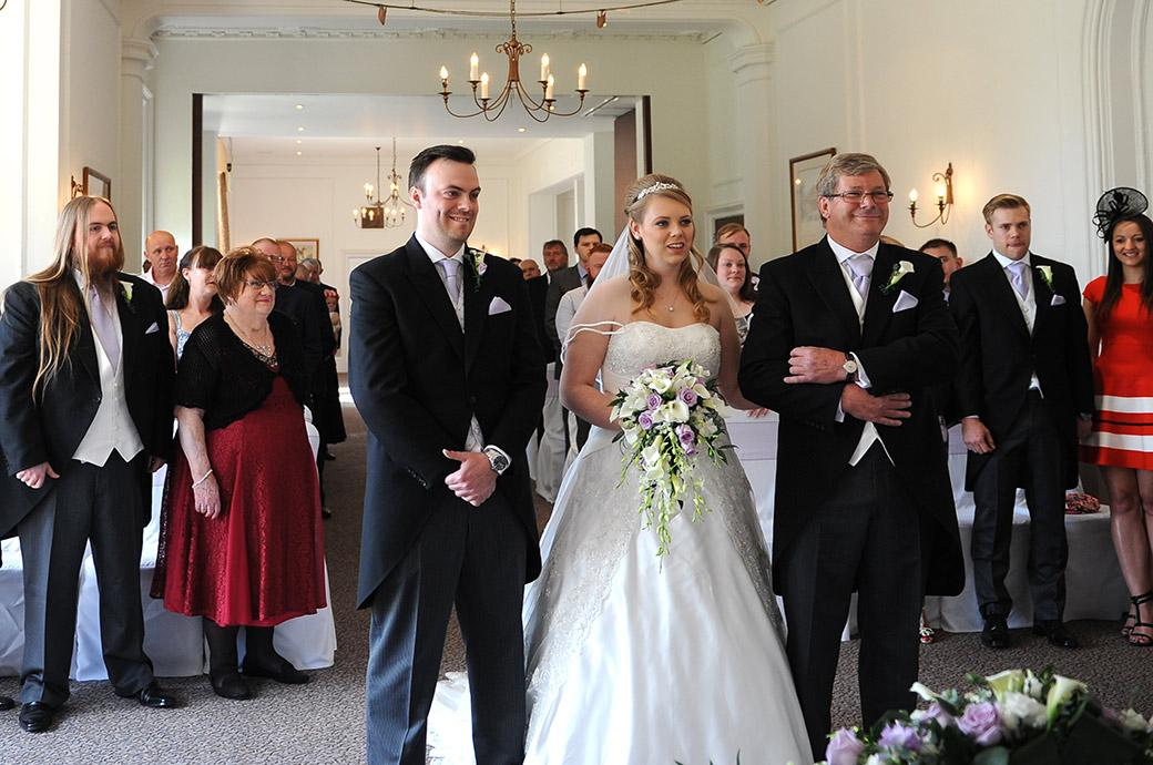 All smiles as the Bride, Groom and father of the Bride stand before the marriage registrar in the Sopwith Room at Surrey wedding venue Horsley Towers