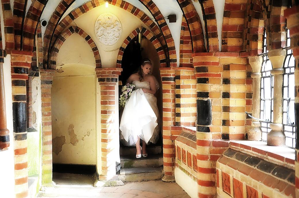 Wedding picture of a bride  at Surrey wedding venue Horsley Towers captured holding up her dress as she descends the steps into the chapel cloisters
