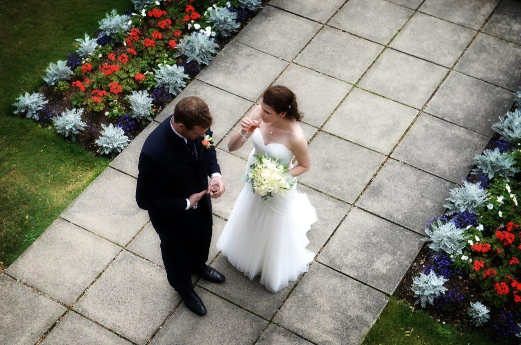 Discrete wedding photograph taken from above of the Bride confiding in her husband in the gardens at Horsley Towers a wonderful relaxed and scenic Surrey wedding venue