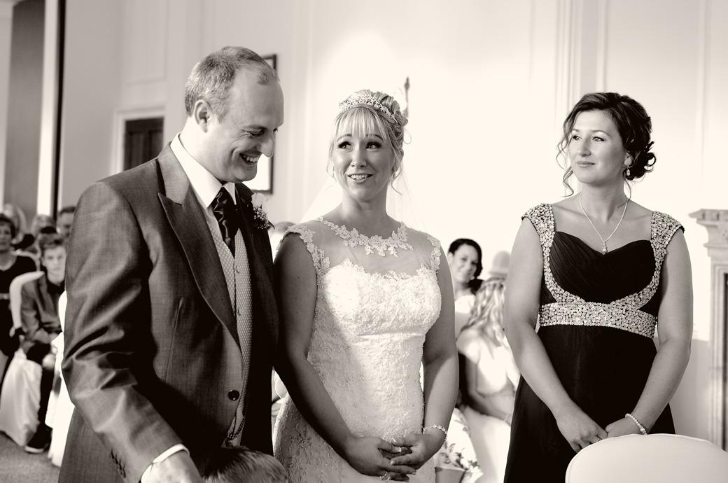 Smiling Bride Groom and Bridesmaid as they stand before the marriage registrar in this relaxed wedding picture captured at the magical Horsley Towers in the Sopwith Room