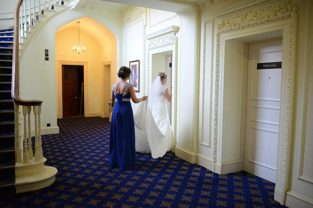 Wedding photograph of the Bride and bridesmaid entering the registrar's room before going down the stairs for the marriage ceremony at Horsley Towers in the Sopwith Room