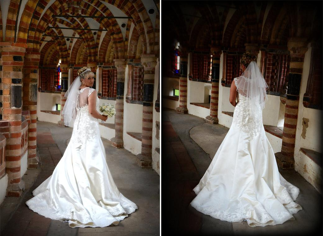 Bride in her beautiful wedding dress captured in these wedding pictures as she walks and looks around in the chapel cloisters taken at the wonderful Horsley Towers in Surrey