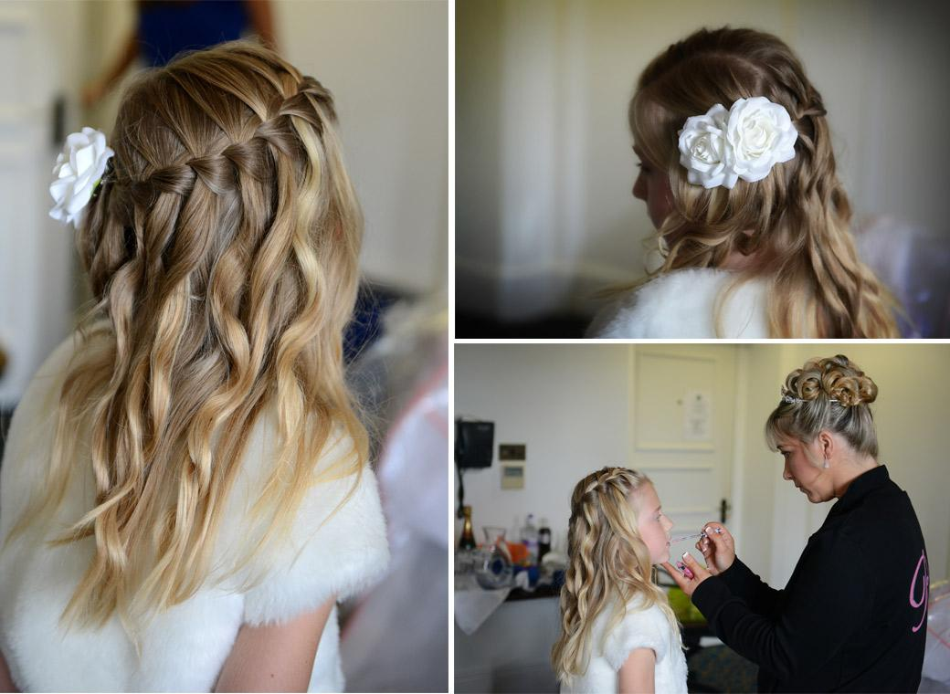 Lovely wedding photos of a bridesmaid with white roses in her beautiful hair having lip gloss applied by the Bride at Horsley Towers captured by a Surrey Lane wedding photographer