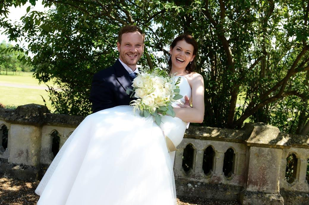 A happy Groom pics up his beautiful laughing wife in this warm and lighthearted wedding picture taken by Surrey Lane wedding photographers in the Horsley Towers garden