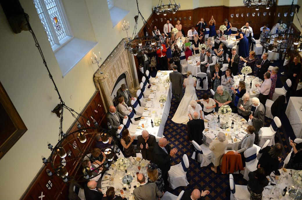 An aerial wedding photo taken from the balcony in the Great Hall at Horsley Towers in Surrey of the Bride and Groom walking past their applauding guests to the head table