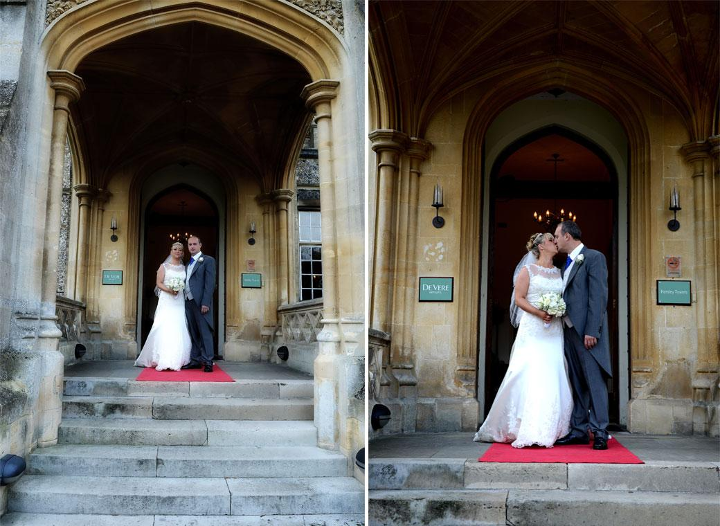 Bride and Groom standing on the red carpet at the front door of the magical Surrey wedding venue Horsley Towers and kissing captured in these two romantic wedding photographs