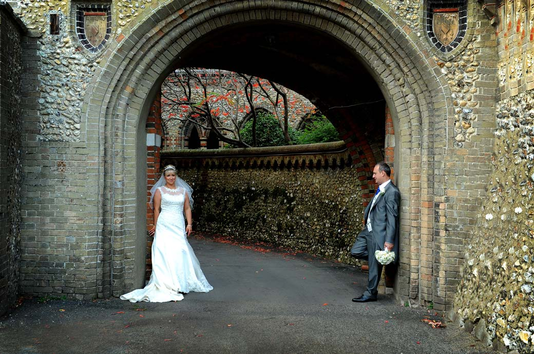 The Bride and Groom posing as they lean on a brick archway in this wedding picture taken at the front of Horsley Towers by a Surrey Lane wedding photographer