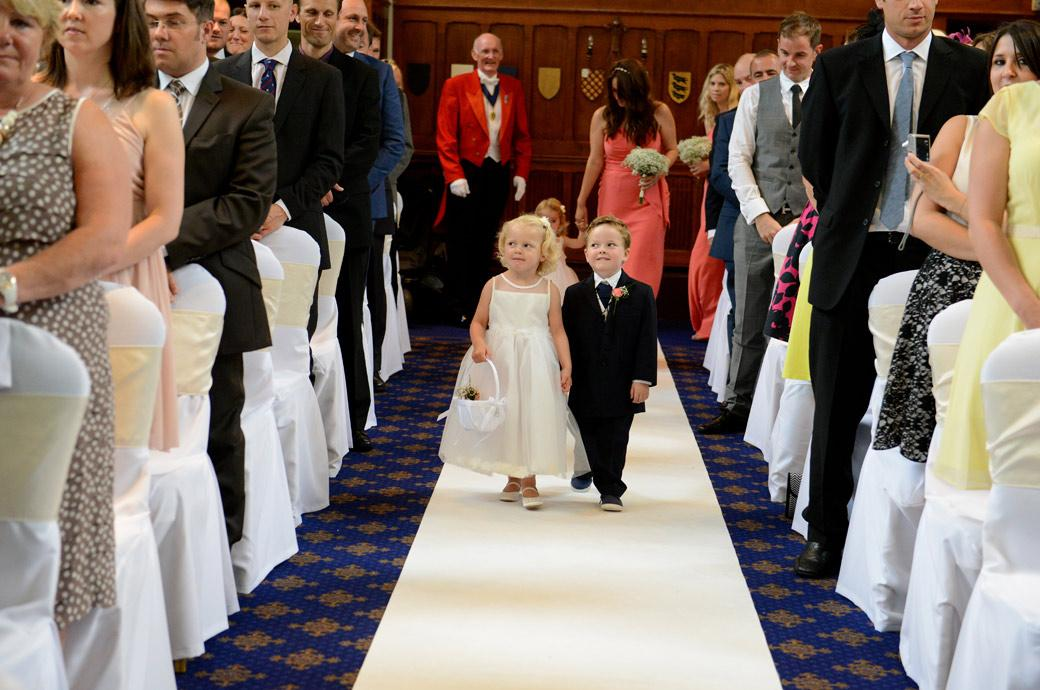 Sweet and cute wedding picture of a pageboy and flowergirl walking down the aisle of the Great Hall at Horsley Towers a fabulous Surrey wedding venue