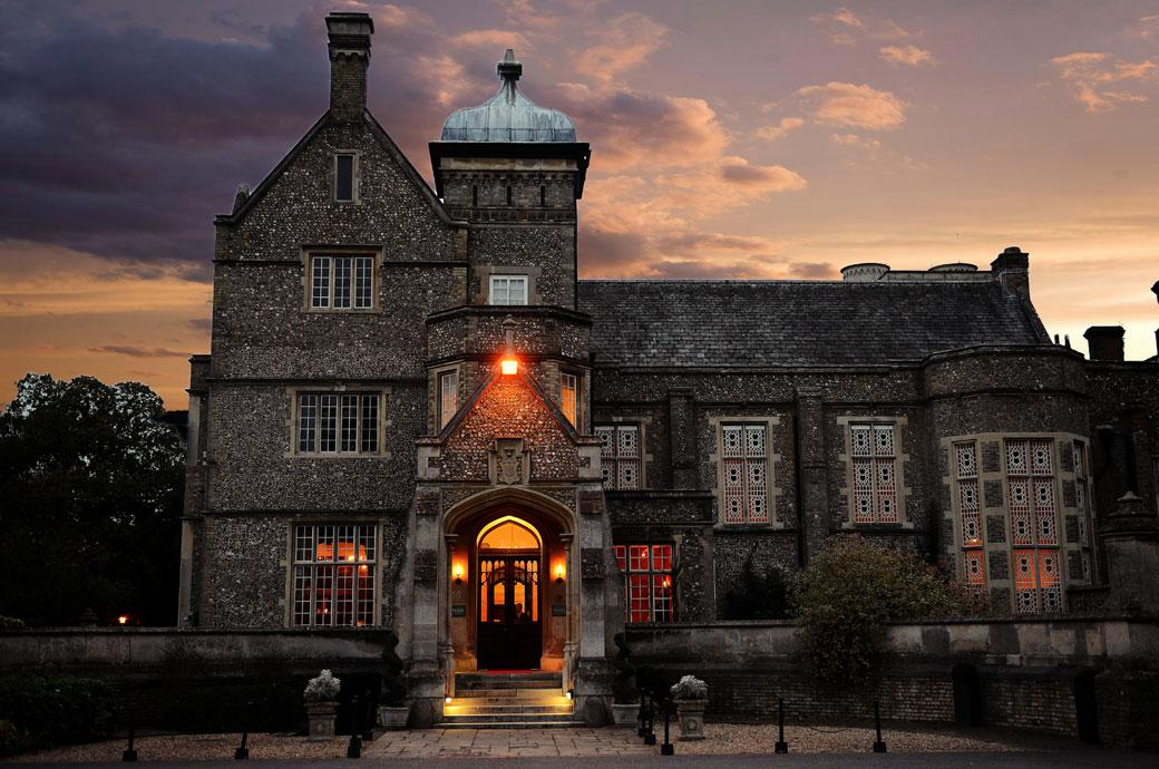 The majestic flint façade with its patterned window shutters glowing at dusk in this atmospheric wedding photo of the magical Surrey wedding venue Horsley Towers