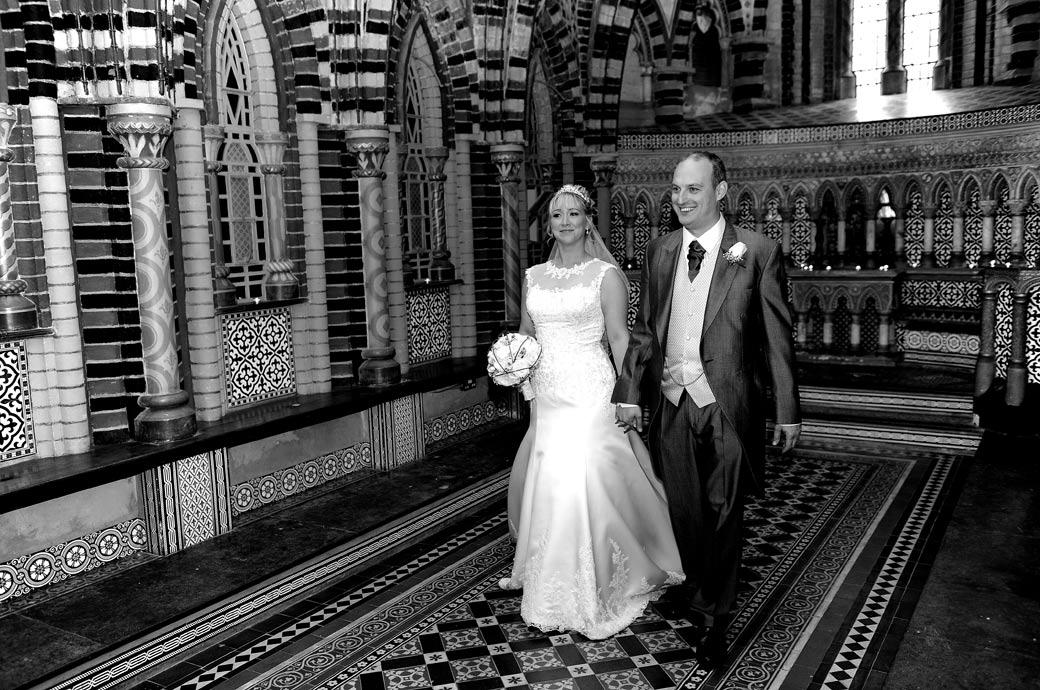 Happy smiling newly-wed couple walk hand in hand in the colourful and ornate chapel in this wedding photo taken by Surrey Lane wedding photographers at Horsley Towers