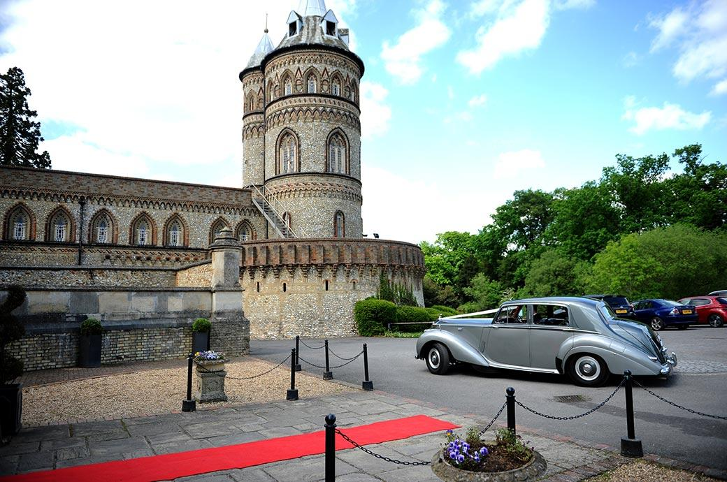 Classic Silver Ghost Rolls Royce bridal car pulls up at the striking Surrey wedding venue Horsley Towers ready for the Bride to alight on the red carpet