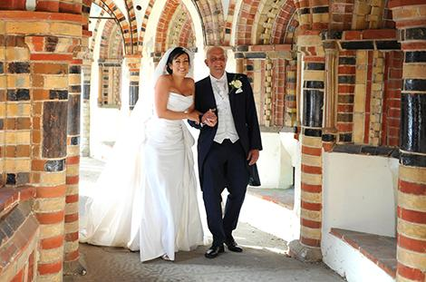 Happy smiling newlywed couple captured at Surrey wedding venue Horsley Towers as they walk down the winding and colourful chapel cloisters
