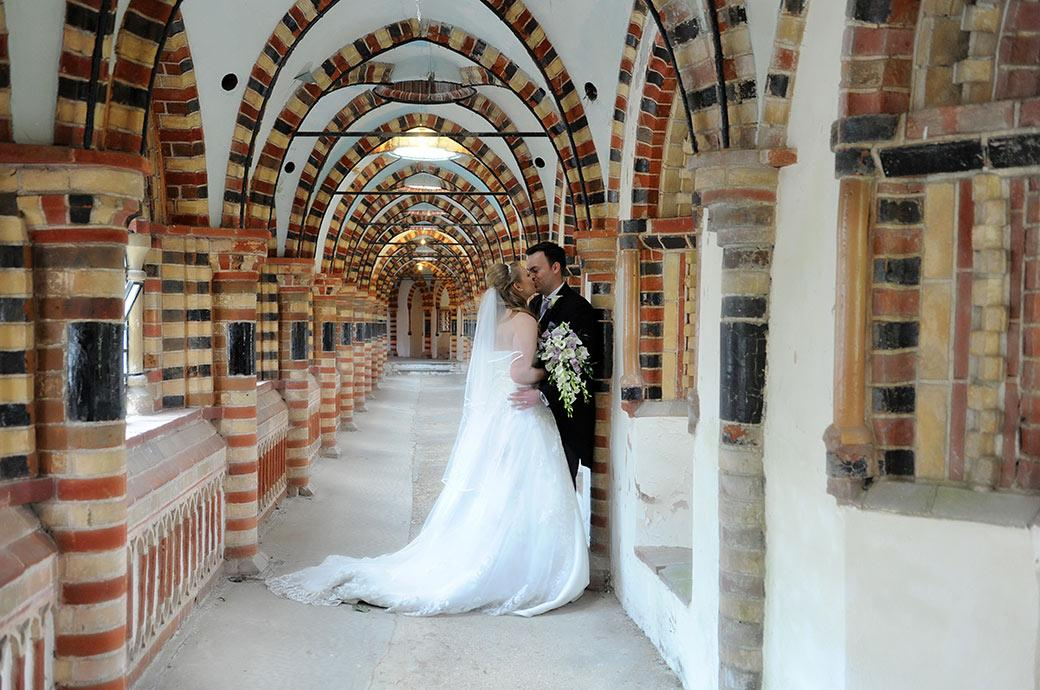 Newlywed couple at Surrey venue Horsley Towers romantically kiss in the fascinating multi brick coloured cloisters leading from the chapel
