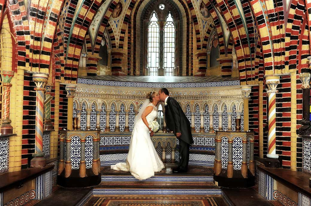 The newly-weds lean forward for a kiss in front of the blues ceramic tiles in this wedding picture taken in the fascinating chapel found at Horsley Towers a Surrey wedding venue with character
