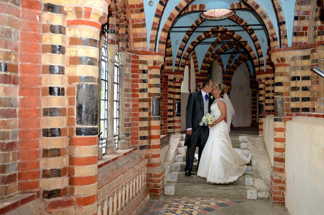Surrey Lane wedding photography capture this romantic moment for the newly-weds as they steal a kiss in this Horsley Towers chapel cloisters wedding photograph