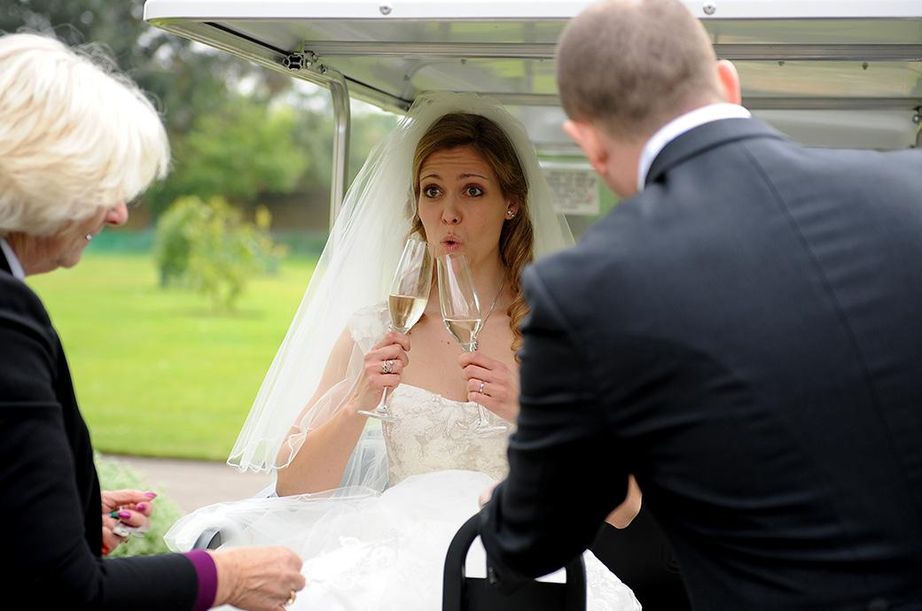 Bride makes fun gesture with two glasses of champagne as she sits in a buggy in Cambridge Cottage Duke's garden Surrey ready for a romantic tour Kew Gardens