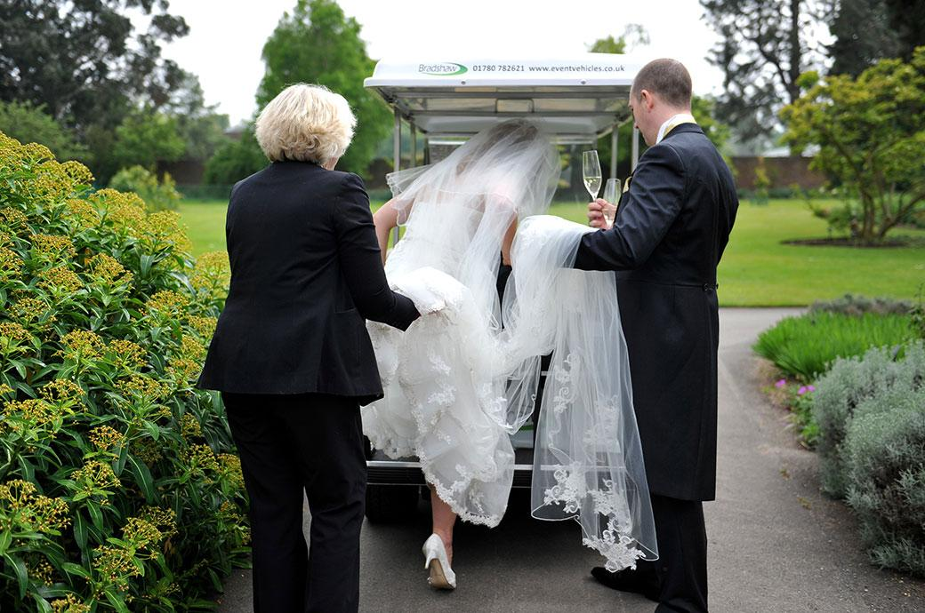 Groom holds the champagne as he helps the Bride at Surrey wedding venue Kew Gardens Cambridge Cottage into the awaiting golf buggy for their romantic mini tour