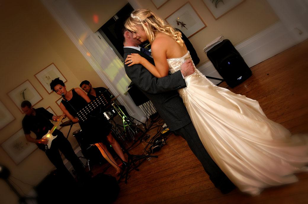 A lovely smiling bride dances with her husband as the band play for the first dance at a wedding in Kew Gardens Cambridge Cottage Surrey