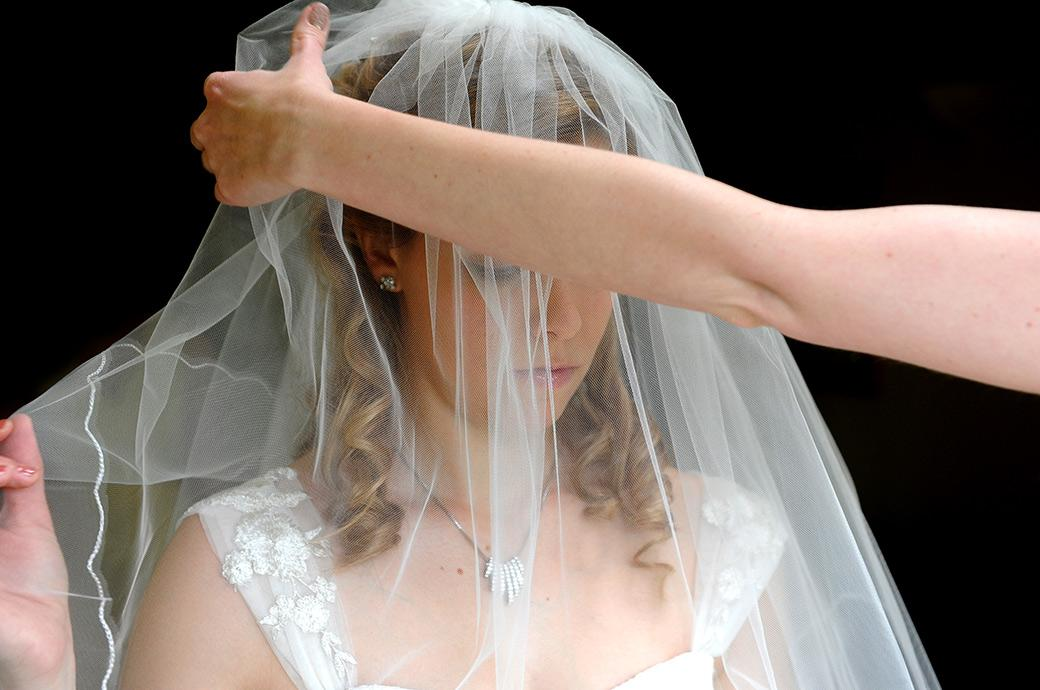 Bride has her veil put over her head by her bridesmaid before leaving home for her marriage at Cambridge Cottage a Surrey wedding venue in the fabulous Kew Gardens