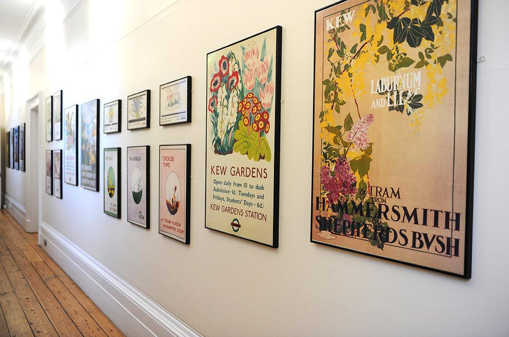 A wall full of colourful London Transport posters advertising Kew Gardens and situated in Surrey wedding venue Cambridge Cottage in The Gallery
