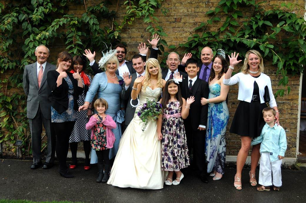 Family give a wave and thumbs up in this fun wedding picture taken by Surrey Lane wedding photographers at Cambridge Cottage Kew Gardens