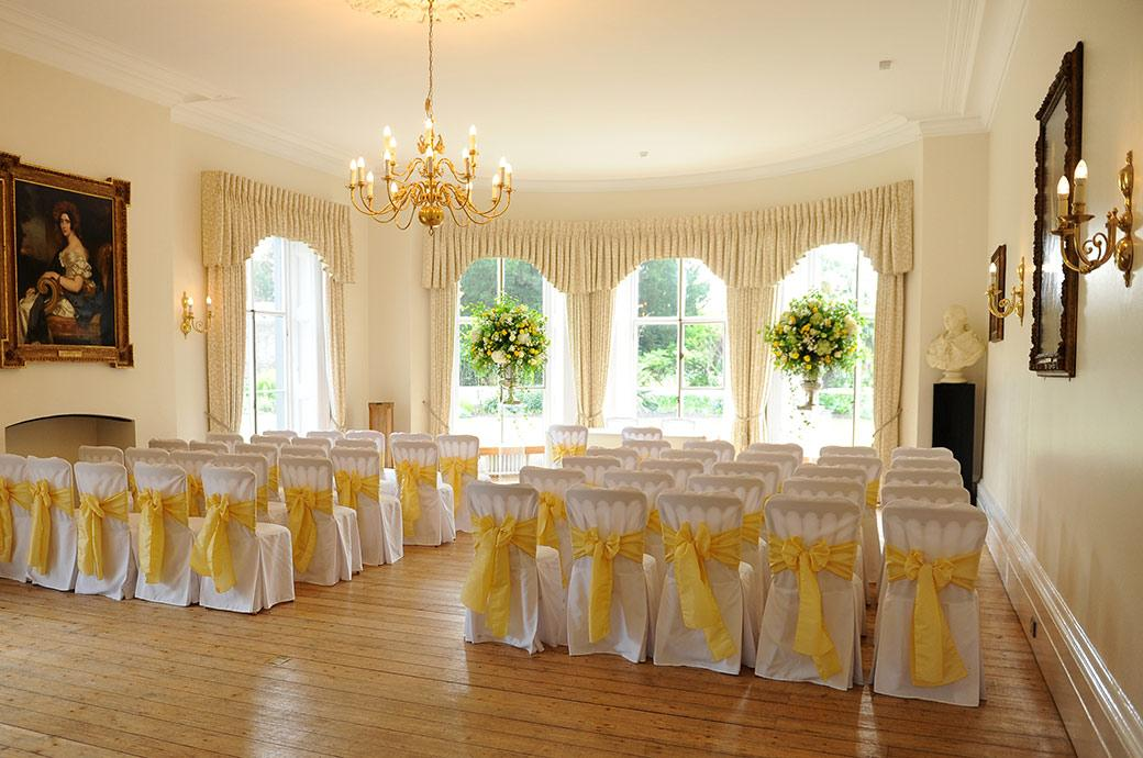 The genteel Drawing Room at the delightful Surrey wedding venue Cambridge Cottage in Kew Gardens dressed in yellow ready for the afternoon's marriage ceremony