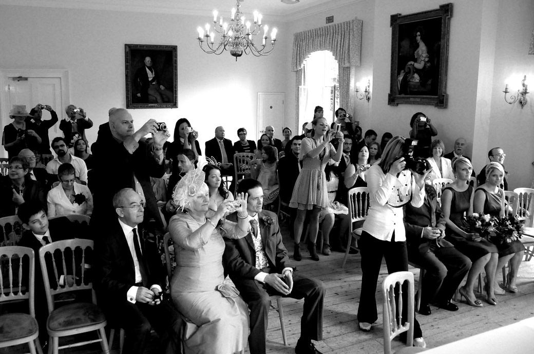 Guests taking photos wedding picture captured in the elegant Drawing Room at Cambridge Cottage in Kew Gardens Surrey wedding