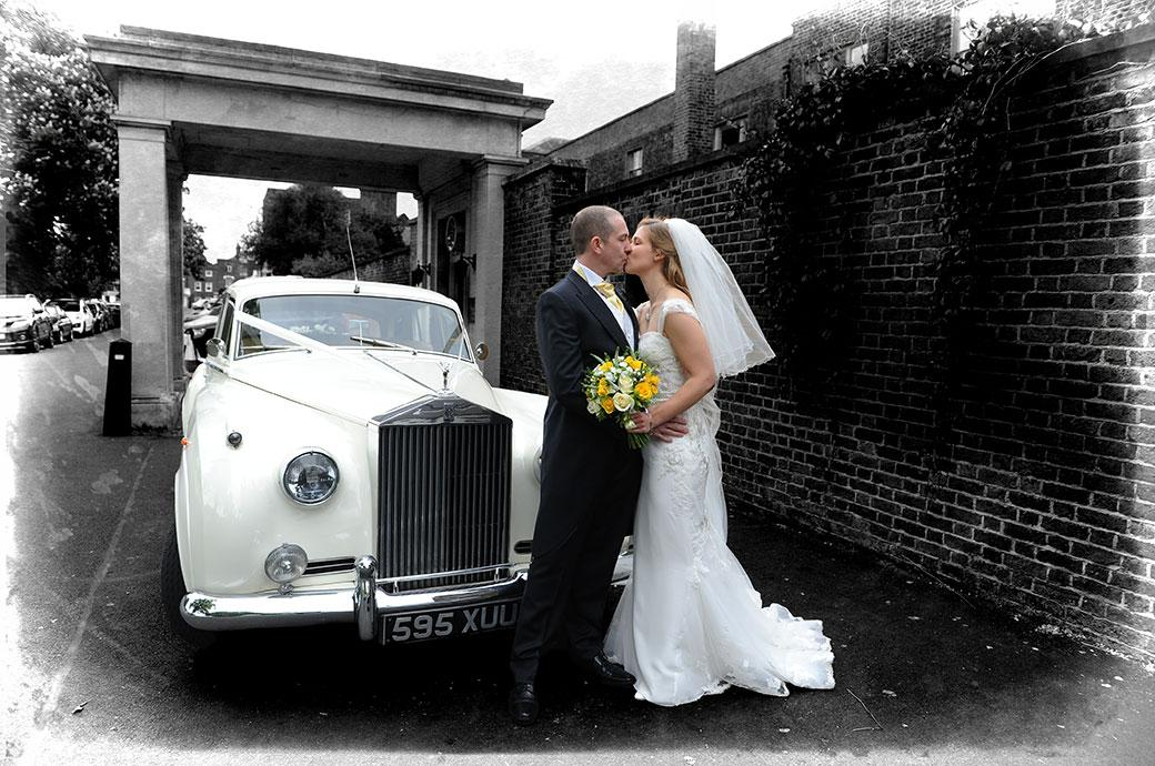 Romantic wedding photograph of a Bride and groom at Surrey venue Kew Gardens Cambridge Cottage kissing in front of their classic white Rolls Royce wedding car