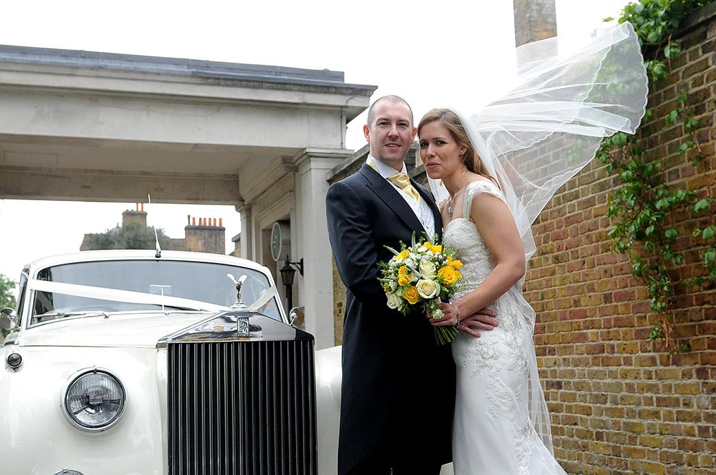 Proud Groom holds his beautiful wife with blowing veil in front of their white Rolls Royce wedding car outside Surrey venue Cambridge Cottage at the world famous Kew Gardens