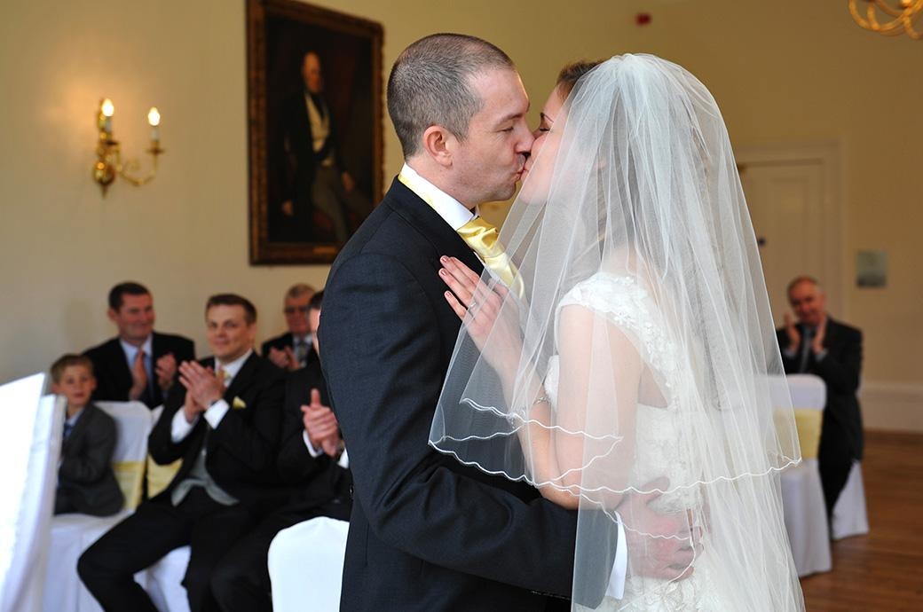 Newlyweds kiss as they are announced husband and wife at the world famous  Surrey wedding venue Kew Gardens Cambridge Cottage in the Drawing room