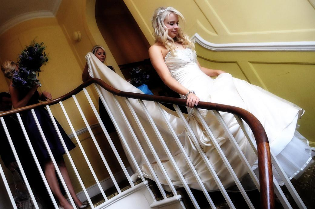 Bride descending stairs in this wedding picture taken at Richmond Gate Hotel as she leaves for Surrey wedding venue Cambridge Cottage at Kew Gardens