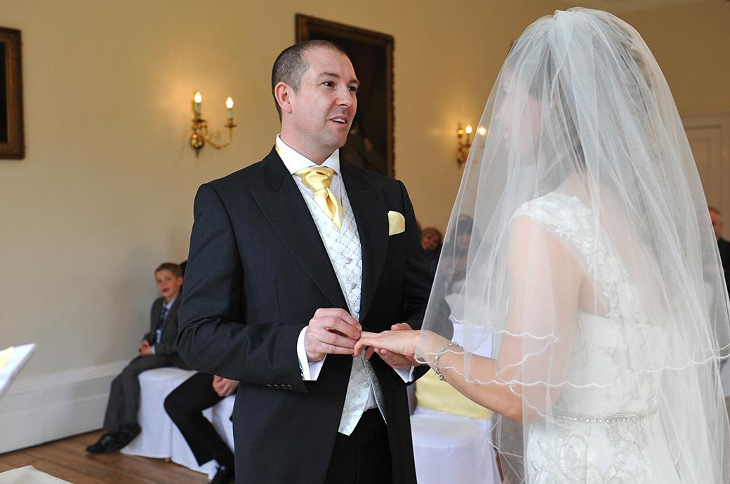 A picture of a Groom holding the ring on his Bride's finger at Surrey wedding venue Cambridge Cottage Kew Gardens as he says his marriage vows