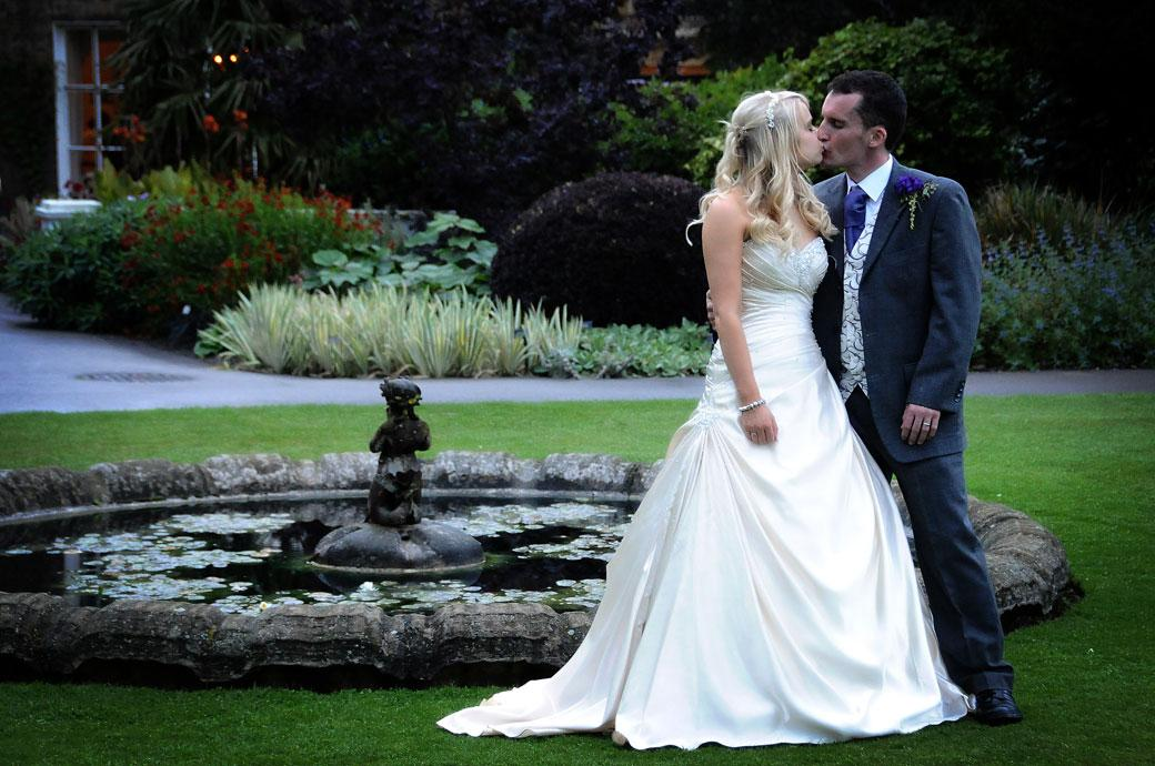 A romantic kiss photo captured in the lovely secluded Duke's Garden by the fountain in Kew Gardens Surrey wedding venue at Cambridge Cottage