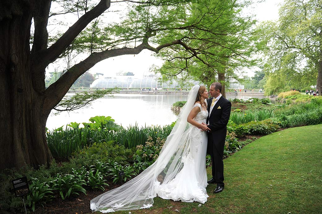 A romantic moment captured of a Bride and groom at Surrey wedding venue Kew Gardens as they stand on the grass by the pond with the Palm House in the background