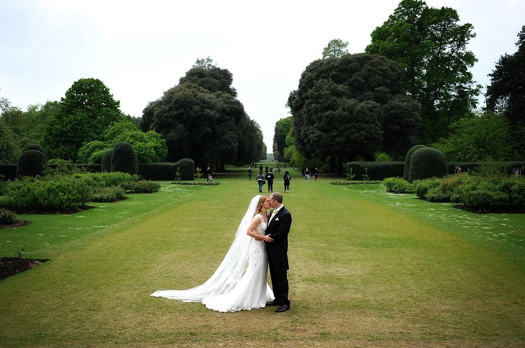 Romantic wedding picture of a Bride and groom kissing on the lawn vista behind the Palm House at the world famous Kew Gardens and colourful Surrey wedding venue