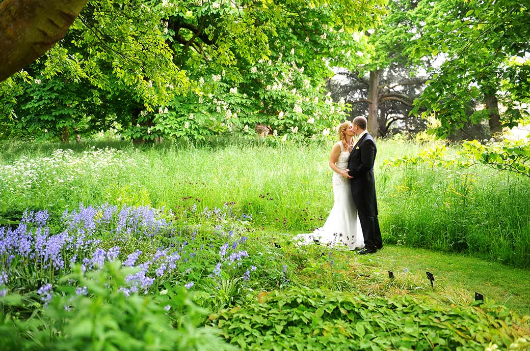 Very romantic wedding photograph of a Bride and groom at Surrey wedding venue Kew Gardens kissing in a little copse lit by sunshine just beyond some bluebells