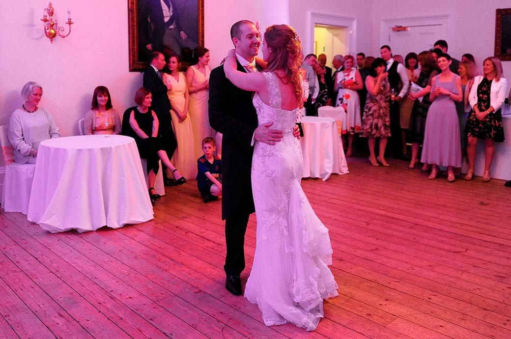 Happy newlywed couple captured at Surrey wedding venue Cambridge Cottage in Kew Gardens start their first dance on the Drawing Room dance floor