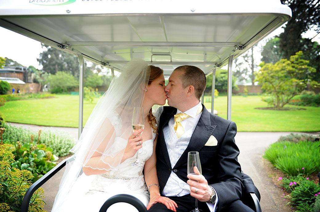 Newlyweds have a kiss with champagne in hand as they sit in their buggy ready to tour the world famous Kew Botanical Gardens Surrey after their wedding at Cambridge Cottage