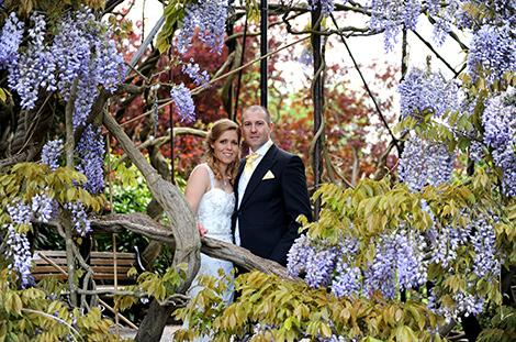 Wedding picture of the Bride and groom at the world famous Surrey wedding venue Kew Gardens framed by this magnificent 200 year old Wisteria tree